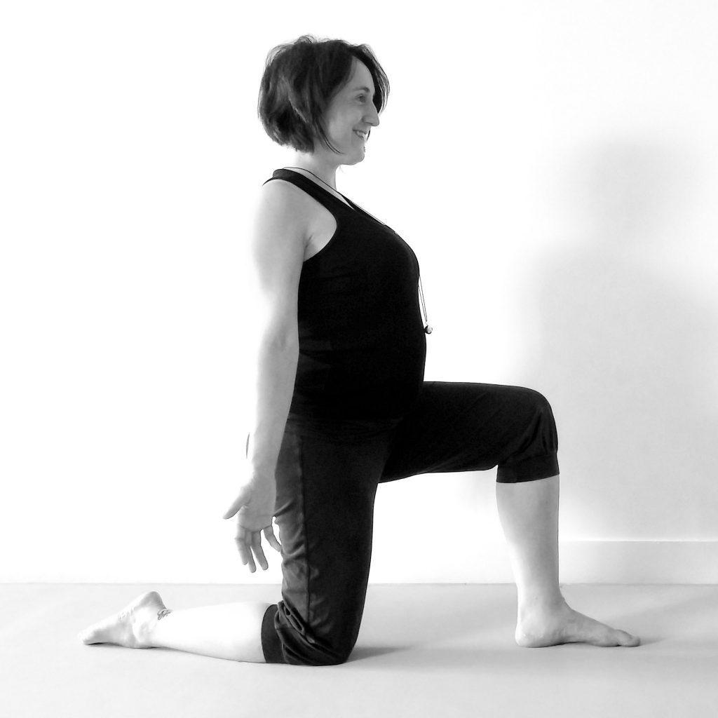 Future maman en posture un genou au sol et en fente avant